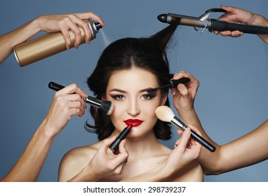 Many hands with cosmetics brush, shadows doing make up of glamour asian girl