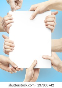many hands holding paper poster on blue background