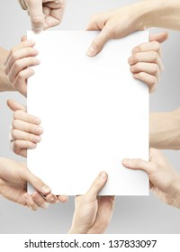 many hands holding poster on gray background