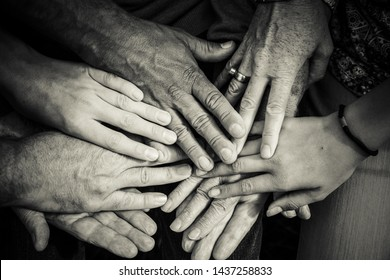 MANY HANDS OF OLD & YOUNG PEOPLE DIFFERENT PEOPLE IN BLACK & WHITE CELEBRATING FRIENDSHIP GENERATION GAP