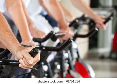 Many hands on bikes in fitness center
