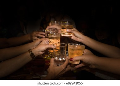 many hands of people holding glass of alcohol in the night party.