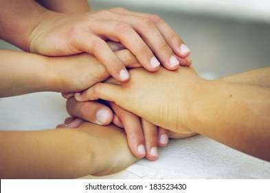 Many hands piled on top of one another in a sign of trustful friendship