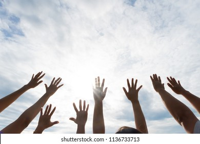 Many hands raised up against the blue sky. Friendship, Teamwork concept.