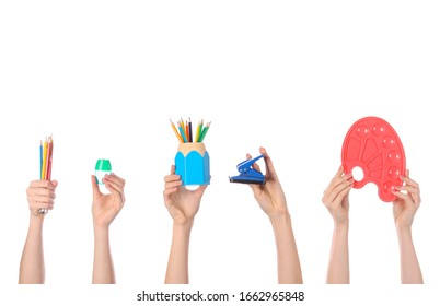 Many hands with school supplies on white background
