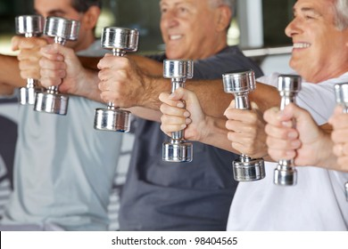 Many hands of senior people holding dumbbells in gym