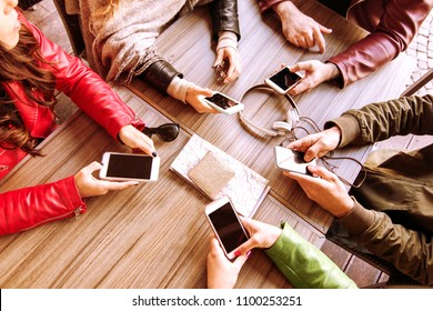 many hands using smartphones in a circle on a table top view. concept of technology, gadgets, communication and connectivity.