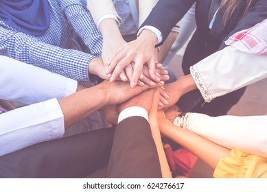 many handshake of young arab business people join hug team work out office . this hand of group corporate mix partnership  multiple ethnicity. Teamwork is importance for successful of business model.