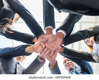 Many handshake of young business people join hug team work out office . this hand of group corporate mix partnership .Businessmen handshake show teamwork view from the bottom up