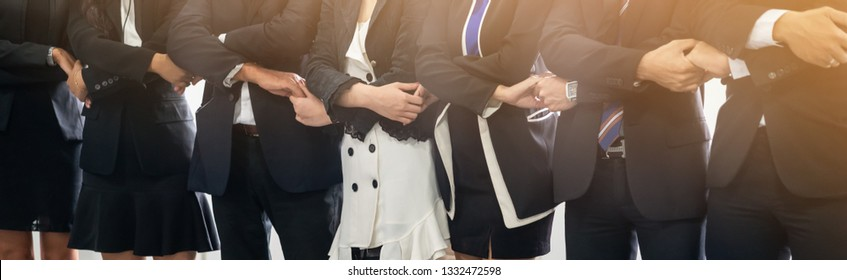 Many happy business people holding hands together with joy and success. Company employee celebrate after finishing successful work project. Corporate partnership and achievement concept.