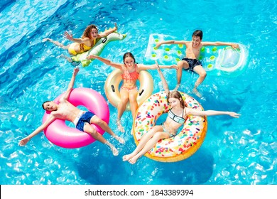 Many happy children friends swim on inflatable ring toys view from above