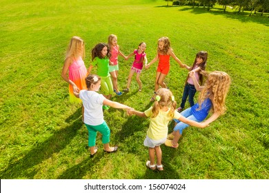 many happy girls play roundelay and dance and stand in circle in the park on the green grass on sunny summer day