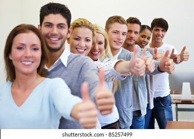 Many happy successful students holding their thumbs up