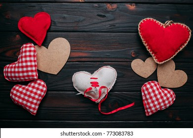 Many hearts on sides and broken heart on the middle of wooden background. Valentines day concept for heartbroken.