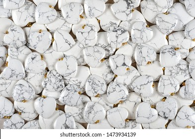 Many heart-shaped semi-precious stones of white howlite as background