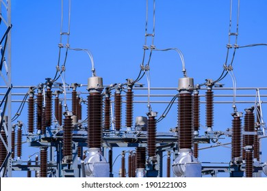 Many high voltage electrical insulators in power substation against blue sky background