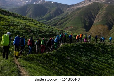 Many hikers are climbing the grassy path with lined shadow and grassy mountain in the background. Springtime in Iran.