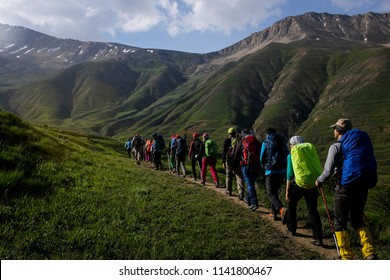Many hikers are climbing the grassy path and grassy mountain is in the background. Springtime in Iran.