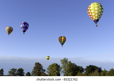 Many hot air balloons floating in the sky