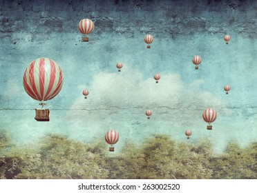 Many hot air balloons flying over a forest