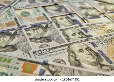 Many hundred American dollar bills lie on a horizontal surface