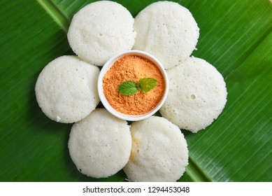 Many Idli or idly with coconut chutney powder popular breakfast of South India and Sri Lanka arranged on banana leaf. Healthy steamed cakes made by steaming fermented batter of black lentils and rice