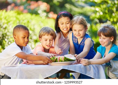 Many interracial kids eating watermelon in summer