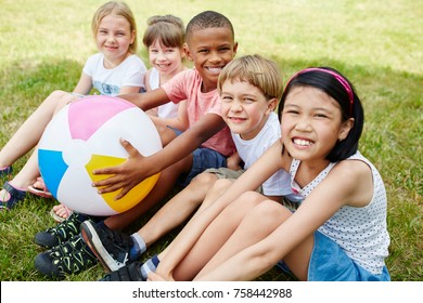 Many interracial kids as friends in the park sitting together in summer