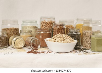 Many jars with grains, seeds, legumes, flours and various food ingredients. Healthy food concept.