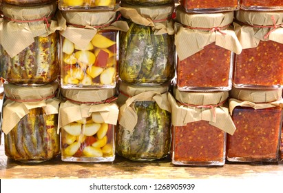 many jars of red sauce of spicy peppers garlic and marinated anchovies prepared by hand in a Mediterranean country