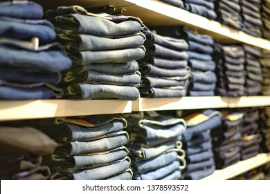 Many jeans in closet. Stack of jeans on shelf. Concept of buy , sell , shopping and jeans fashion .