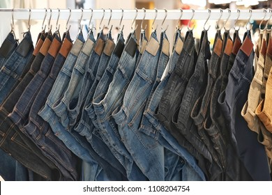 Many jeans hanging on a rack. Row of pants denim jeans hanging in closet. concept of buy , sell , shopping and jeans fashion .