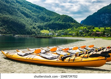 many Kayak placing on the shore with Gudvangen fjord in background under bright sky, a village in the municipality of Aurland in Sogn og Fjordane county, Norway. It is a popular tourist