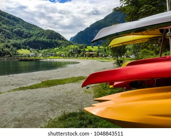 many Kayak placing on the shore with Flaam fjord in background under bright sky