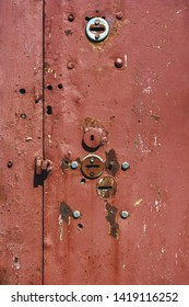 Many keyholes in the old iron door. Traces from inaccurate installation of locks.