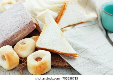 Many kinds of bread on wooden boards.
