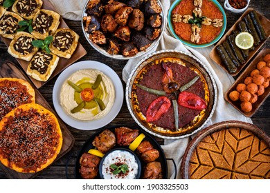 Many kinds of food and meze on the dining table. Local foods named Sini kebabı and tepsiye et basma. Traditional foods concept.