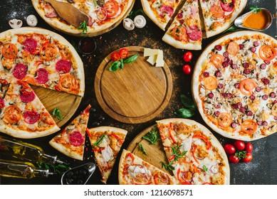Many kinds of tasty pizzas on black background. Flatlay. Copy space
