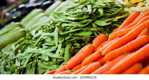 Many kinds of vegetables on the local produce fruit and veg market. Includes runner beans, courgette, lemon, pepper, tomato, chilli, onion, carrot, lemon,  aubergine and many more.