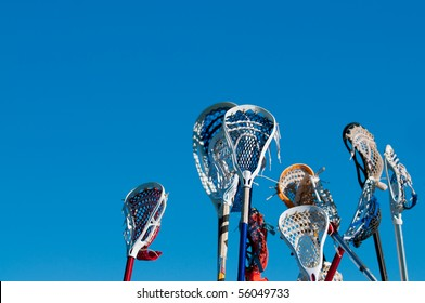 Many lacrosse sticks in the air prior to a game starting