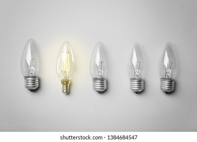 Many lamp bulbs on light background, top view. Symbol of idea and solution