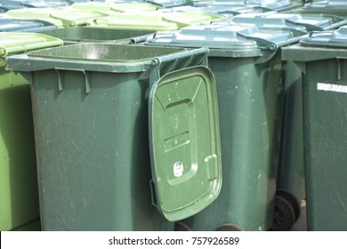 Many large multi-colored plastic garbage containers on wheels