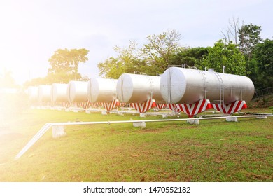 Many large oil or gasoline tanks are placed on the grass, sky background.
