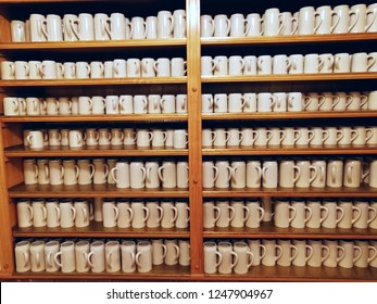 Many large white beer cups stand on a shelf in a pub.