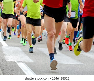 many legs of runners during the race on the street of the city