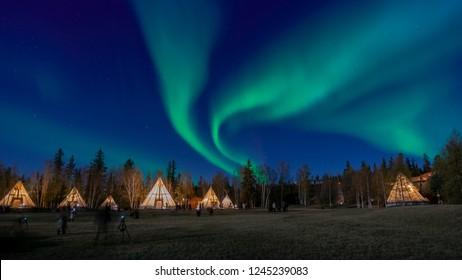 Many lightup Tipi with Aurora Borealis at Yellow Knife, Canada