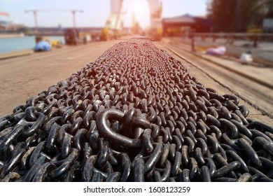 many lines of used rusty heavy iron chain, view of an big anchor and big chain on the ground lined