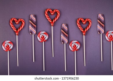Many lollypops, striped lollypop looks like an ice-cream, round swirled and hart shaped  on a stick on violet background. Flat lay style.
