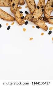 many long pieces of bright yellow and orange biscotti with white and black sultanas and nuts, dried sweet crispy italian bread On the upper part of vertical shot on the white background with copyspace