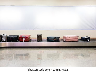 Many luggages are laying down on the conveyor belt at the airport. Baggage claim. White wall background.